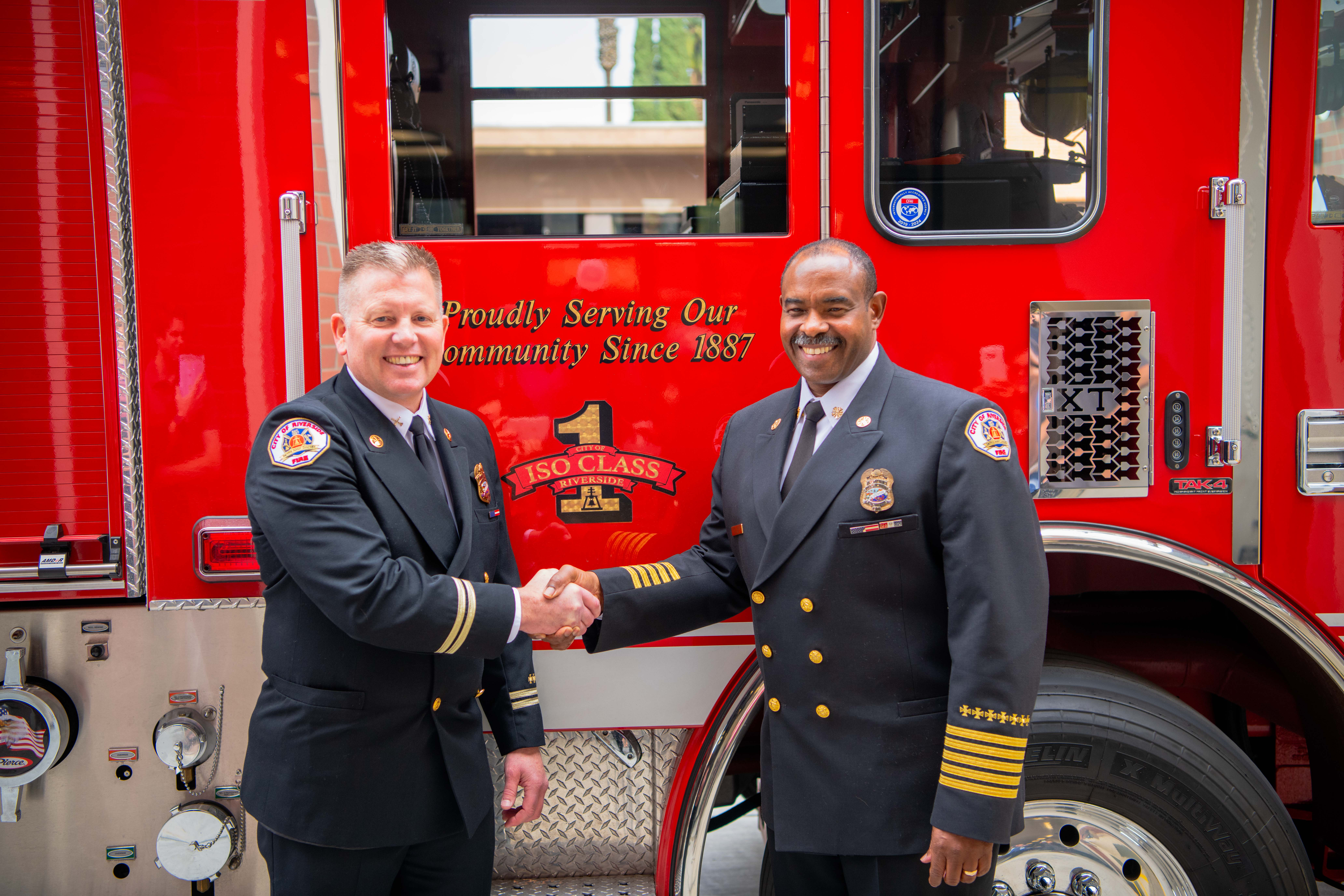 Chief Moore shaking hands in front of a fire engine with Chief Gooch
