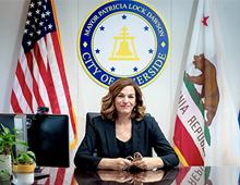 Mayor Patricia Lock Dawson at desk with, City of Riverside Seal, U.S.A and CA flags behind her